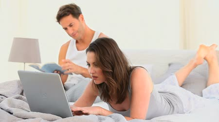 ležící : Woman working on her laptop lying on the bed while her husband is reading a book