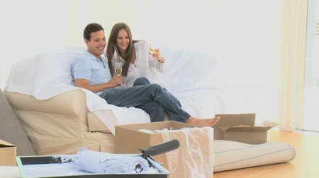 flet : Happy couple drinking champagne while unpacking