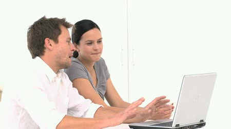 looking : A young couple looking at something on their laptop against a white background