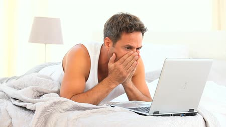 megrémült : Anxious man on his laptop on his bed