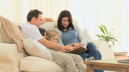 фото : Lovely family looking at an album sitting on the sofa at home