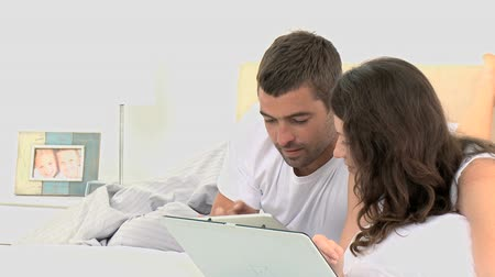 girfriend : Couple looking at a computer tablet while their are lying on the bed
