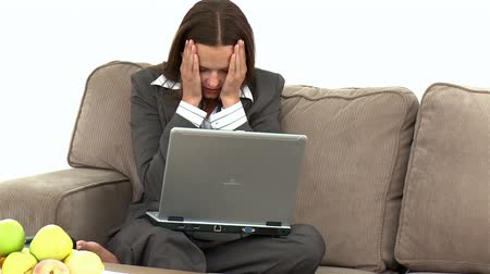 kanapa : Worried businesswoman having made a mistake on the laptop sitting on the sofa at home Wideo