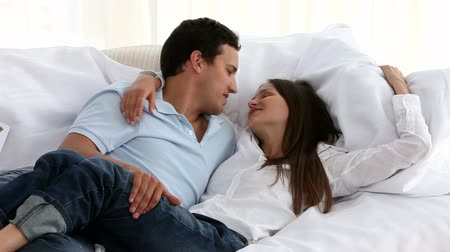объятие : Happy couple lying on the couch and hugging each other at new home