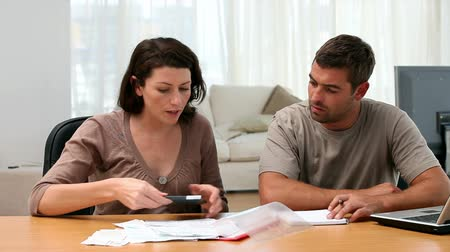 impostos : Couple calculating bills in the livingroom