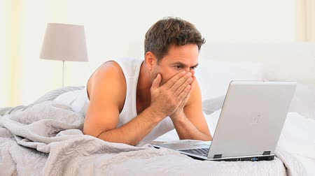male : Angry man is on his laptop at home