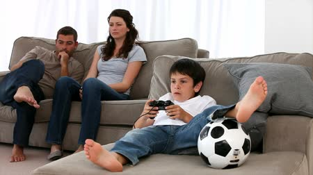 дичь : Son enjoying video game and parents enjoying watching on the sofa Стоковые видеозаписи