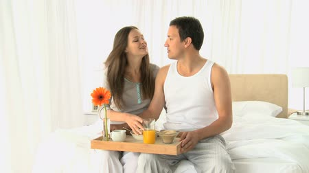 любовь : Lovely couple having breakfast sitting on the bed at home Стоковые видеозаписи