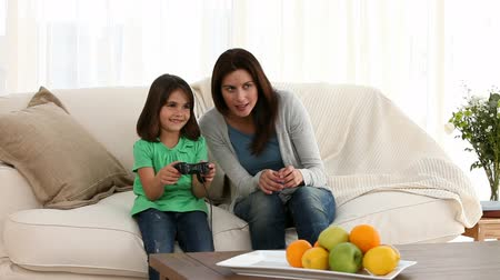 eğlence oyunları : Mother and daughter playing video games on the sofa