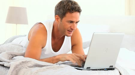 male : A very angry man on his laptop on his bed