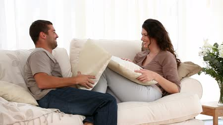 zakochana para : Man and woman doing a cushion fight in the sofa isolated on a white blackground Wideo