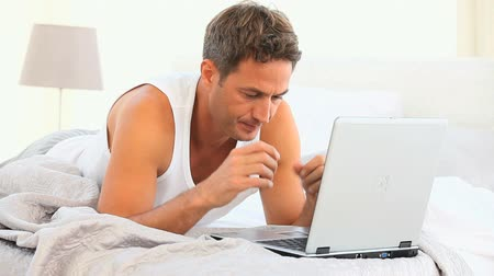 беспокоюсь : Anxious handsome man working on his laptop on his bed