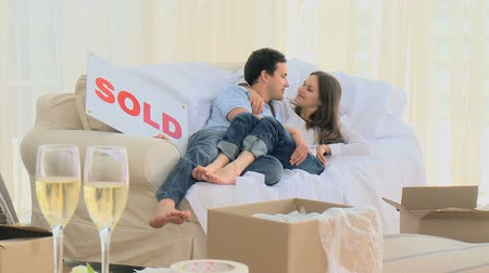 real : Lovely couple lying on the sofa and kissing each other at new home