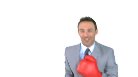 isabet : Joyful man giving punches with boxing gloves in front of the camera against a white background