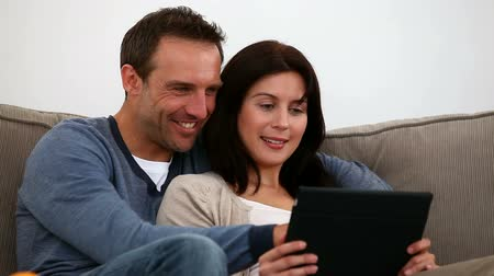 impostos : Couple speaking together on the sofa in the living-room Stock Footage