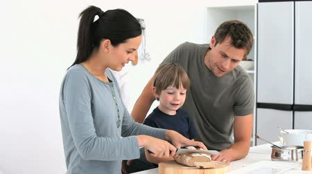 vacsora : Adorable family cutting bread in the kitchen