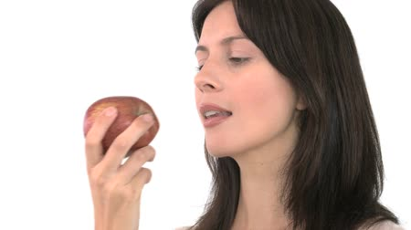 eat background : Smiling woman eating an apple against a white background Stock Footage