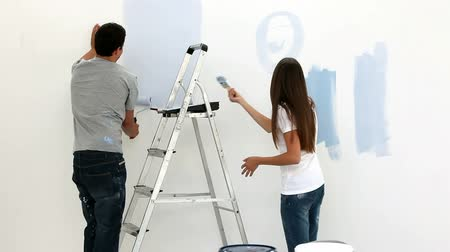 papel de parede : Happy couple painting wall in blue in their bedroom