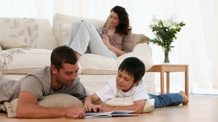 mamãe : Father and son looking a book on the floor and mother on the sofa in the living room Stock Footage