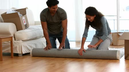 halı : Happy couple rolling a carpet of the living-room