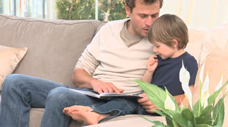öykü : Man reading a book with his son in the livingroom