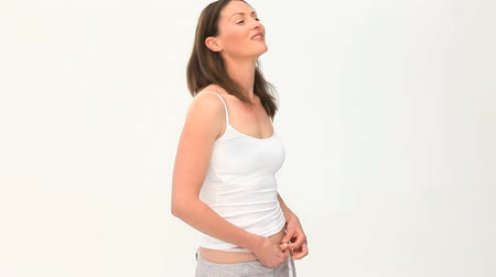 fogyás : Woman excited by her waistline against a white background
