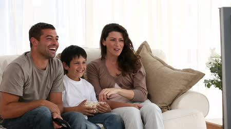 dívat se : Loving family watching television sitting on sofa in living room