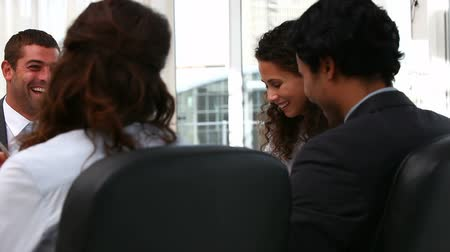 employee : Team laughing in a meeting in a office