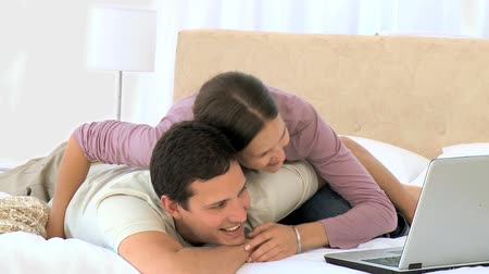 объятие : Woman hugging her husband while he is working on his laptop Стоковые видеозаписи
