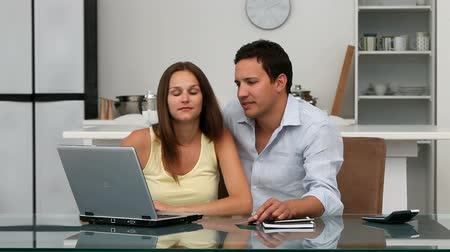surfing the net : Couple buying on internet with a credit card sitting at a table in the kitchen