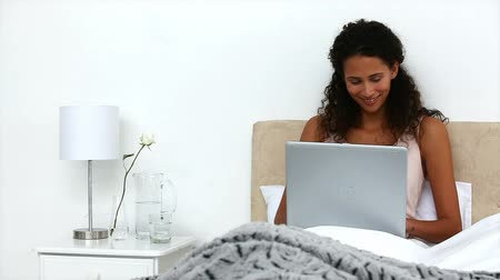 cobertor : Beautiful woman working with a laptop in the bed isolated on a white background