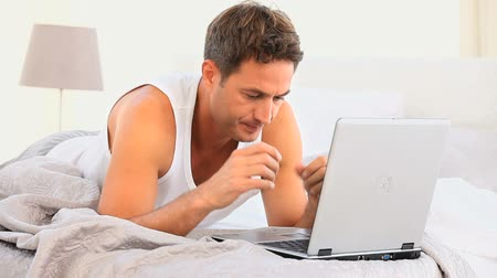 bosszús : Annoyed man working on his laptop lying on the bed Stock mozgókép