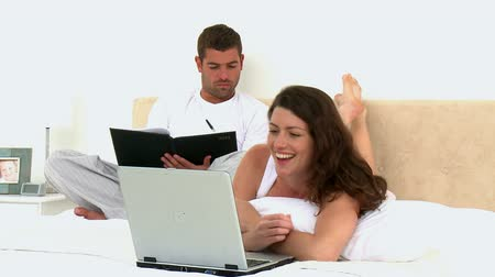 postel : Couple looking video on the computer while they are lying on the bed at home