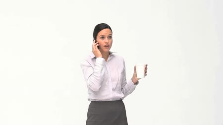 colarinho branco : Businesswoman drinking while she is phoning against a white background Stock Footage