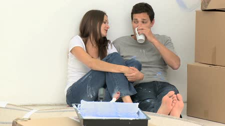 nowe mieszkanie : Happy couple drinking coffee on the floor during the renovation of a room