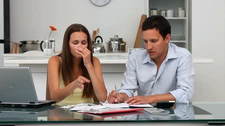 беспокоюсь : Worried couple paying their bills sitting at a table in the kitchen Стоковые видеозаписи