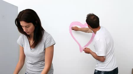 святой : Man drawing a heart on a white wall for his girlfriend