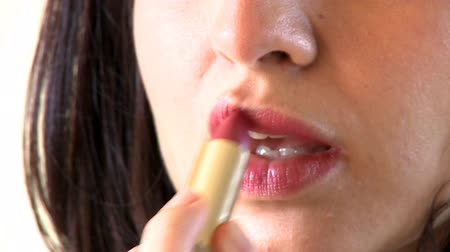 ruj : Close-up of a charming woman putting lipstick against a white background Stok Video