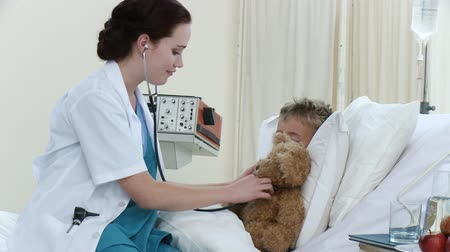 maci : Footage in high definition of beautiful doctor talking and playing with a little boy recovering in hospital. Concept of healthcare