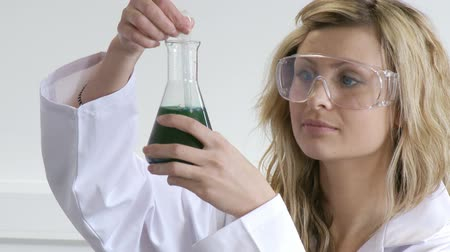 ученый : Blonde woman looking at chemicals