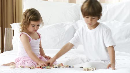 bloklar : Footage in high definition of little siblings playing with toy cubes in bedroom