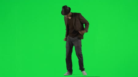 biodro : Footage of an ethnic young man dancing with a hat and a jacket against green screen in high definition