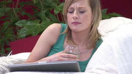 repousante : Stock Video Footage of a Woman unwinding with a Glass of Wine on the Sofa