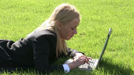irodai dolgozó : Stock Video Footage of a Woman lying on grass using laptop computer
