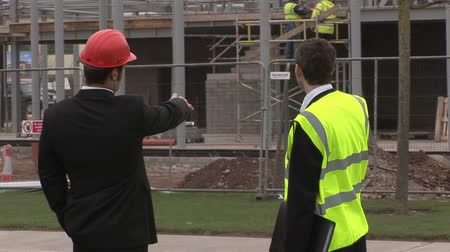 properties : Two engineers in discussion at a Construction Site Stock Footage