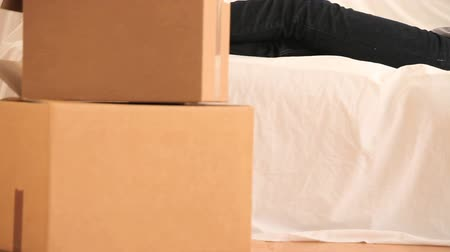 tektura : Young woman resting surrounded by boxes