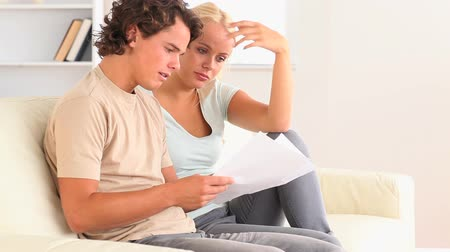 banknoty : Couple looking at a document while sitting on a sofa Wideo