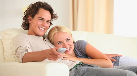 assistindo : Cute couple watching TV in the livingroom