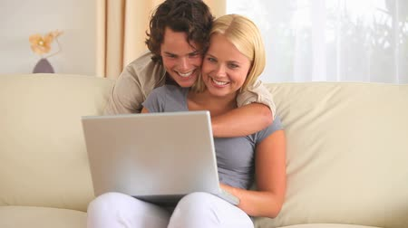 megölel : Hugging couple looking at a laptop in the livingroom Stock mozgókép