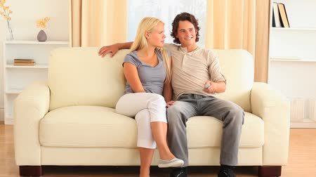 konfor : Happy young couple on the sofa fighting for remote in the livingroom